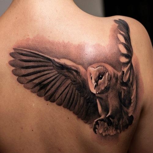 татуировка сова с распахнутыми крыльями на спине